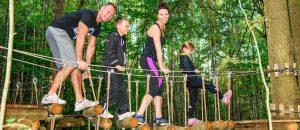 Familie, som er ude at klatre i trætopper